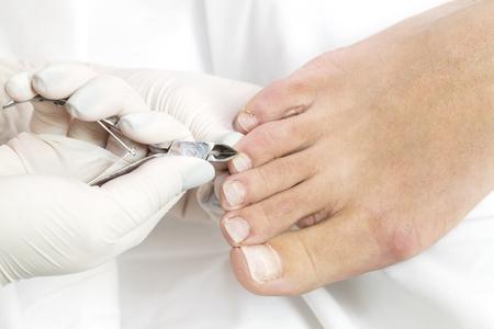 Female foot in the process of pedicure procedure in a beauty salon closeup.
