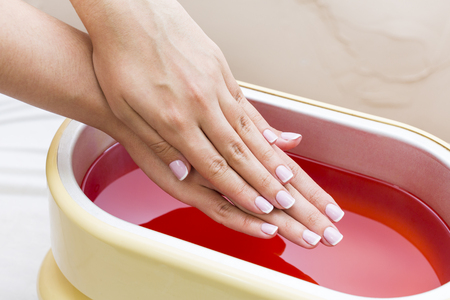 Process paraffin treatment of female hands in beauty salon Stok Fotoğraf - 92407310
