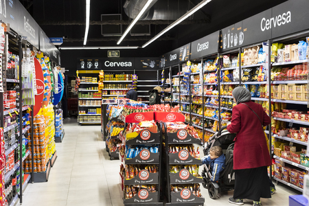 BARCELONA, SPAIN - 11 JANUARY 2018: Visitors and products on the shelves of the shelves and refrigerator of the grocery supermarket Carrefour.