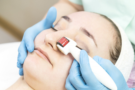 The woman undergoes the procedure with a modern medical instrument derma roller
