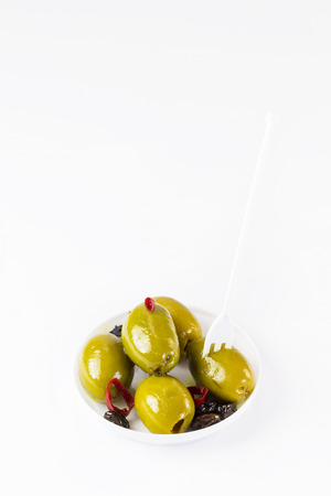 Olives in a small plastic plate on a white background. Stock Photo