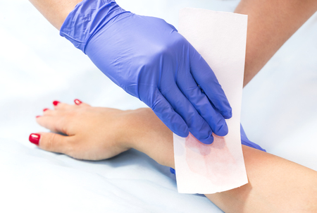 The process of classical wax depilation of the female limbs in the beauty salon. Stock Photo