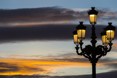 Lighted lanterns against the backdrop of the setting sun on the streets of Madrid Stock Photo