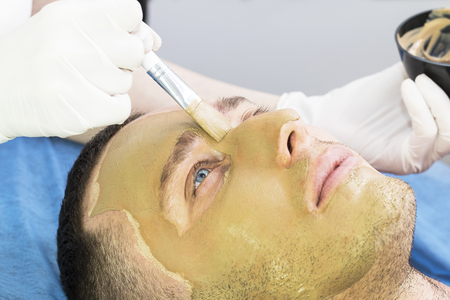 A man does the procedure cleaning his face with a clay mask in the beauty salon 写真素材