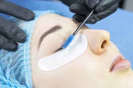 Woman on the procedure for eyelash extensions, eyelashes lamination.