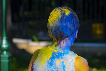 Portrait of a boy in blue and yellow paint at the celebration of the Holiday Holi Stock Photo