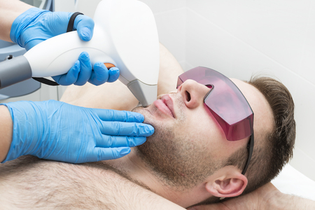 Man on the procedure of laser hair removal in the beauty salon Stock Photo