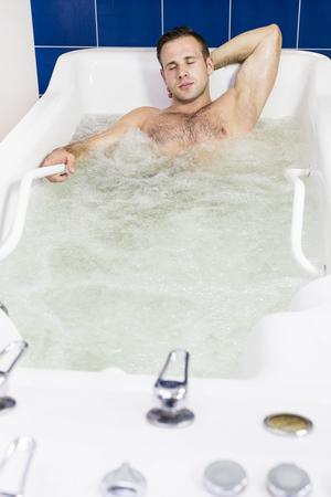 The young man is the procedure in the whirlpool hydrobath Archivio Fotografico