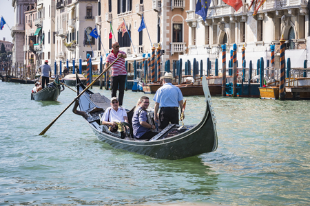 ITALY, VENICE - 5 SEPTEMBER, 2018: Men in gondoliers with tourists in Venice in Italy.