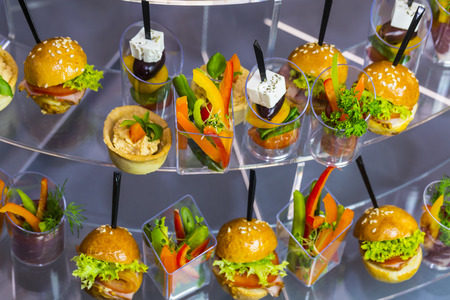 Mini canapes with cheese salads and seafood in plastic cups. Banco de Imagens