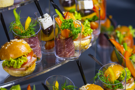 Mini canapes with cheese salads and seafood in plastic cups. Stock Photo