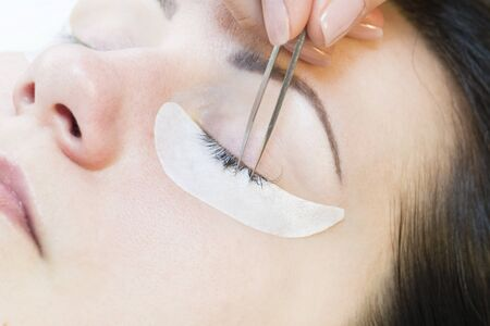 The procedure in the beauty salon eyelash extension and laminating woman.