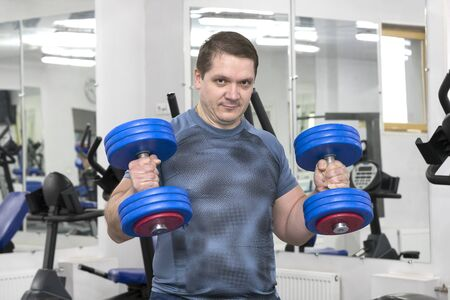 Middle-aged man goes in for bodybuilding in the gym.
