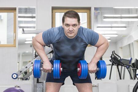 Man van middelbare leeftijd gaat voor bodybuilding in de sportschool.