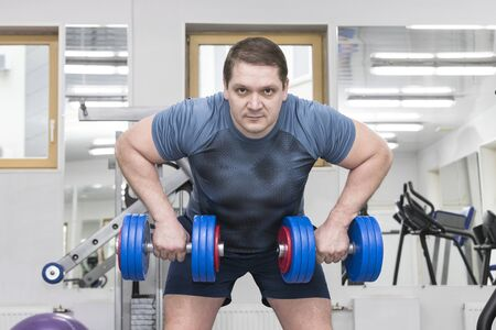 Un homme d'âge moyen se lance dans la musculation dans la salle de gym.