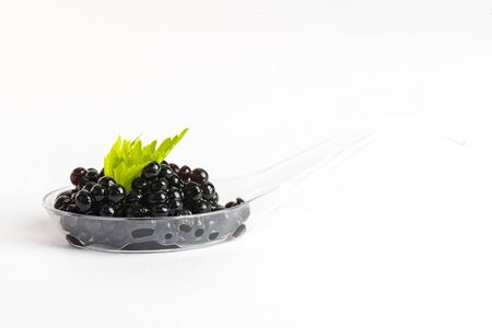 Molecular cuisine caviar elements shot closeup of a plastic buffet table spoon. 版權商用圖片