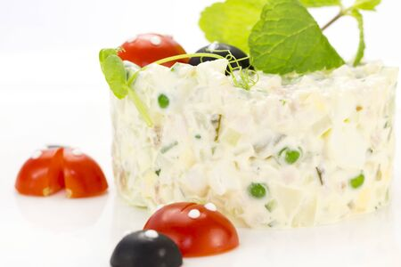 Olivier salad decorated with tomatoes on a white