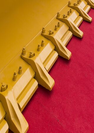The metal part of the excavator bucket is shot close up on a red carpet Imagens