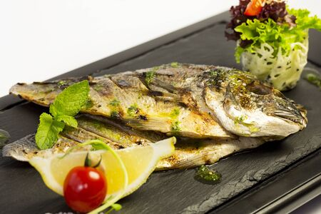 Grilled sea fish on grey table Banque d'images