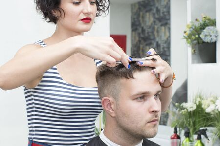 Woman haircuts a young guy in a hairdresser.