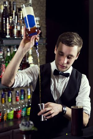 A young guy working as a bartender behind a bar is preparing drinks for customers.