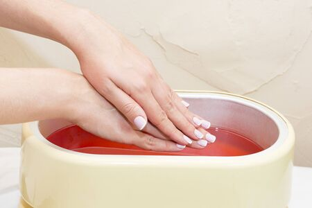 The process of paraffin therapy of a female hand is shot close up in a beauty salon. 스톡 콘텐츠 - 149005612