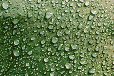 Rain water droplets on green color fiber waterproof fabric. Green background. Stock fotó