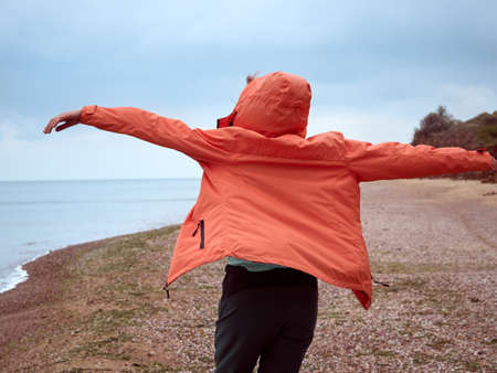 The adventures of alone girl in a coral raincoat on the seashore
