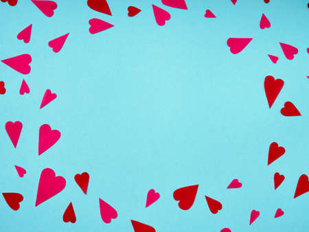 Top view on red and pink paper hearts in corner on blue background with copy space Standard-Bild