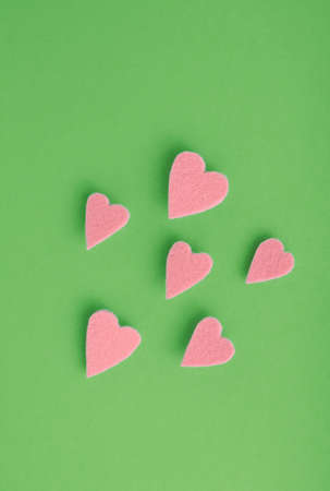Isolated felt hearts soar over a green background with copy space