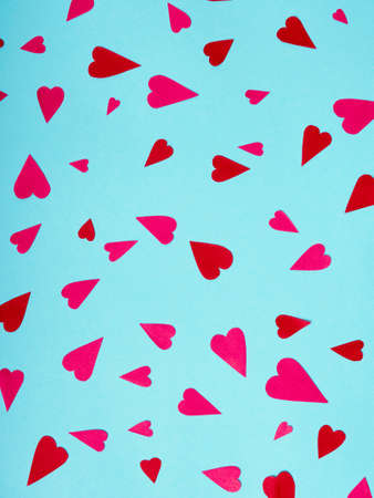 Top view on red and pink paper hearts on blue background