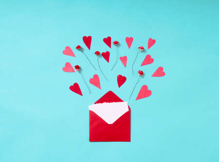Isolated envelope with paper red roses and heart on a blue background with copy space Standard-Bild