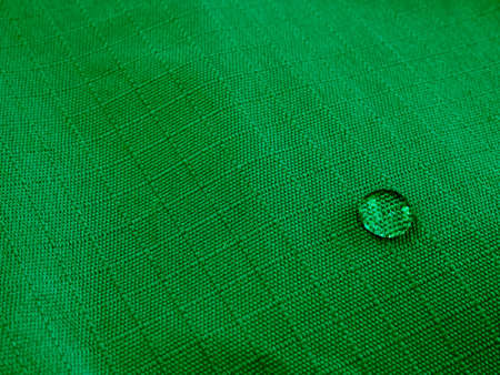 Water drops on waterproof membrane fabric. Detail view of texture of green waterproof cloth.