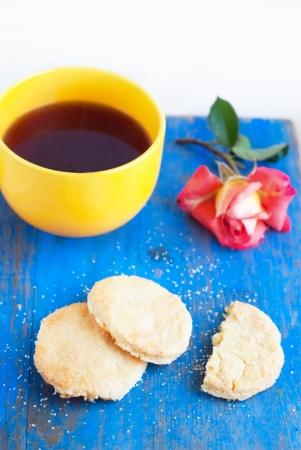 Shortbread, gelbe Tasse mit starkem Tee und stieg photo