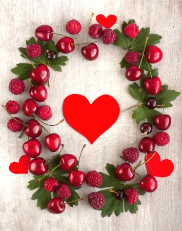 bacca: Red heart in the frame with rich summer berry and green leafs Stock Photo