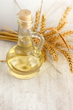 sunflower oil in the glass jug and ears of wheat photo