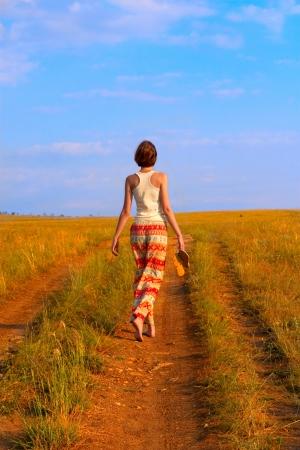 earth road: Snella giovane donna a camminare sulla strada di terra