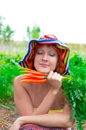 oddity: dreamy woman with bunch of fresh carrots