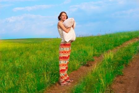 earth road: Giovane donna snella con il cuscino sulla strada terra Archivio Fotografico