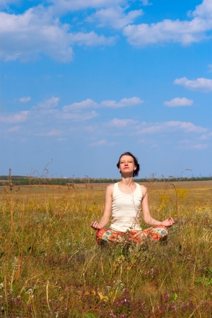 beatitude: young slender woman meditate  in the meadow