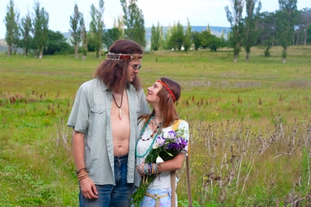 infatuation: couple hippie in love with flowers on the meadow Stock Photo