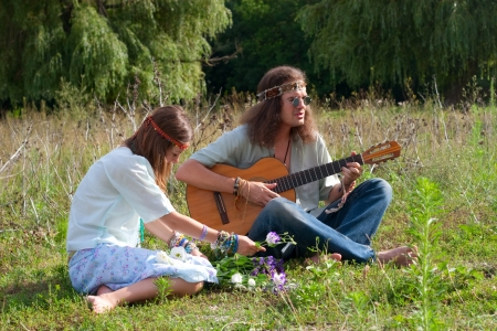 hippy: young hippie men play on the guitar and sing, young hippie women twine a wreath with flowers