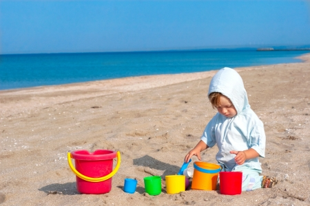 small children: small child play on the beach with different size toy bucket Stock Photo