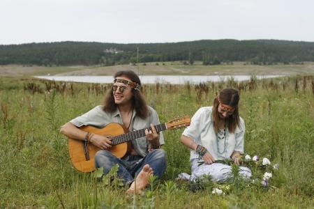 mujer hippie: j�venes hippies juegan en la guitarra y cantar, joven hippie hacen una corona de flores