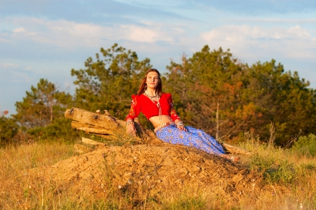 hillock: beautiful Gipsy in the red short top siting on the hillock Stock Photo