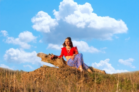hillock: beautiful young  hippie siting on the hillock in front of the sky Stock Photo