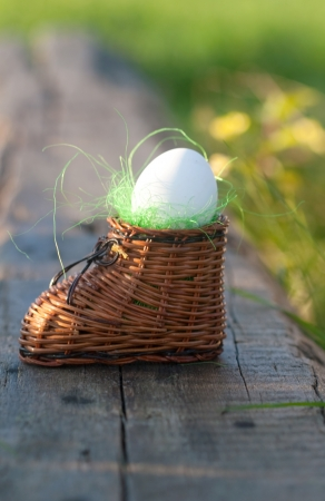 small articles: hard-boiled egg in the nest in the wicker small shoe Stock Photo