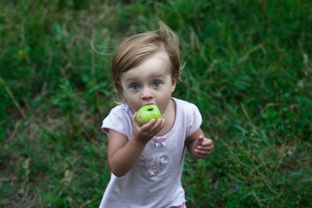 masticate: funny little girl with green apple Stock Photo