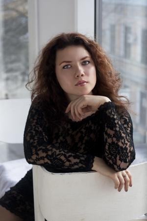 womanhood: woman in the black dress sit by window