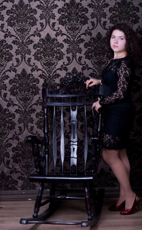 aristocratic: aristocratic woman in the black dress by wood chair